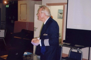 Picture of the speaker wearing a captains uniform.