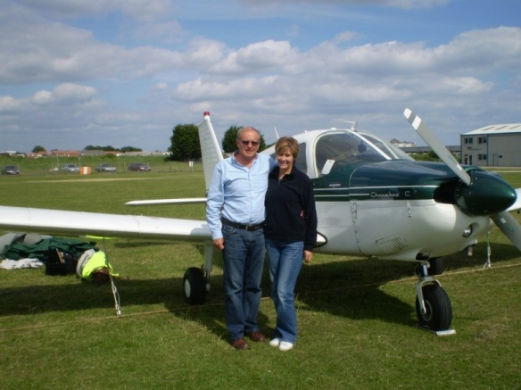 Piper Cherokee G-ATIS on the ground with a man and a woman standing in front.