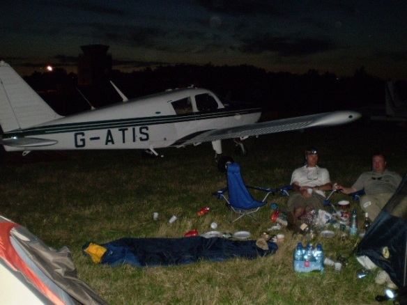 Cherokee G-ATIS parked in front of a a group of people sitting in camp chairs.