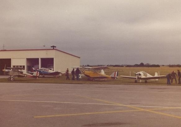 Four light aircraft, two of them biplanes, ligned up in front of a hangar.