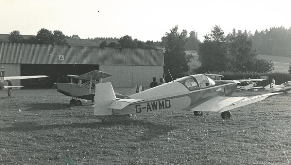 A jodel (registration G-AWMD) with a Currie Wod behind it, a number of other aircraft and a hangar in the background.