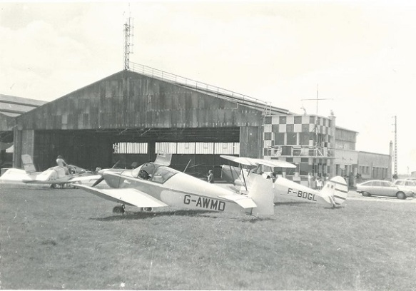 A Jodel (G-WMD) and a biplane (F-BDGL) parked on grass in fron of an open hangar.