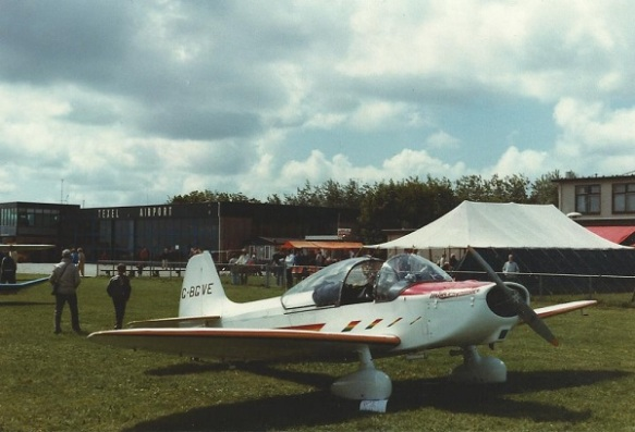 An Emeraude aircraft parked on grass, canopy open with a marquee in the background.