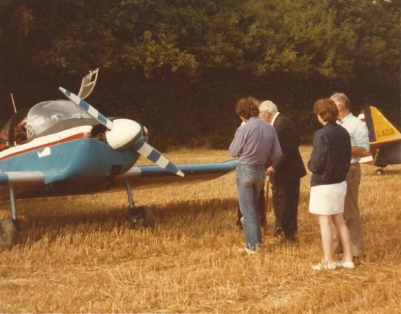 A group of four people standing talking in front of a small aircraft.
