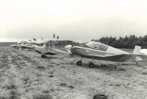 A monocrome picture of a row of light aircraft parked on a dry crass field.