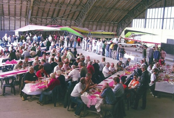 A large group of people sitting eating at tables layed out in an aircraft hangar, a number of weight-shift microlites in the background.