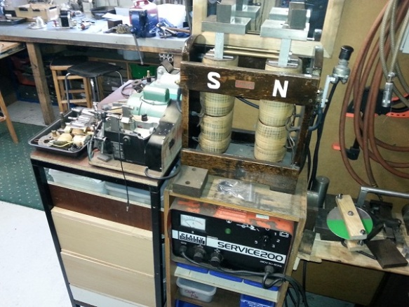 A woodent frame on top of a stack of equipment with two coils labled 'S' and 'N'.