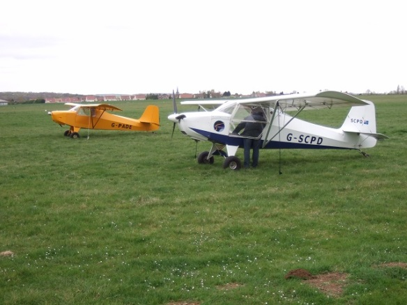 A yello and white Escapade aircraft parked on grass.