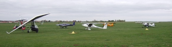Three aircraft parked on grass.