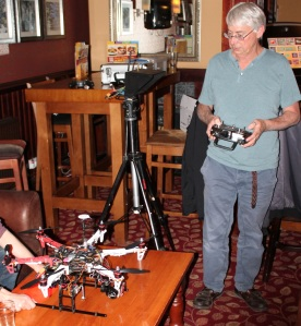 A man holding a radio control handset in front of a hexacopter on a bar table.
