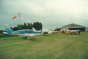 A row of light aircraft parked in fron of a windsock and hangar.