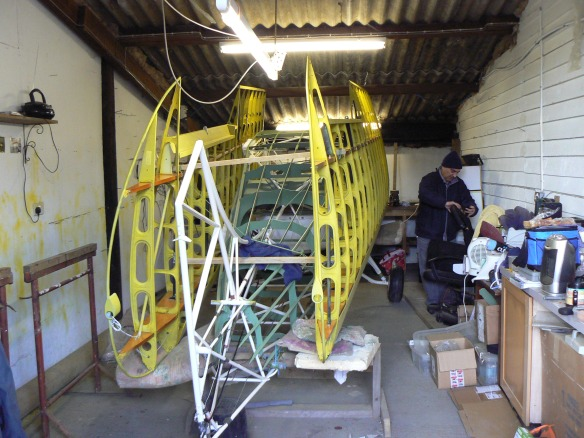 Uncovered aircraft in shed.