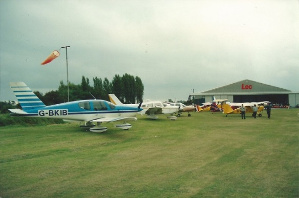A number of light aircraft parked on grass by a windsock, a hanger with the sign 'Lec' painted on it in the background.