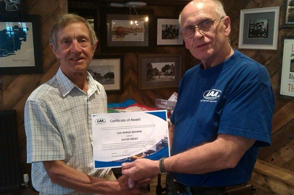 Two elderly men, the one on the right handing a certificate to the one on the left.