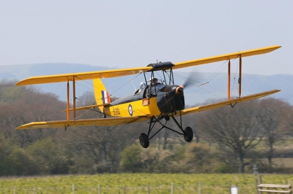 A yello Tiger Moth in flight approaching a runway threshold.