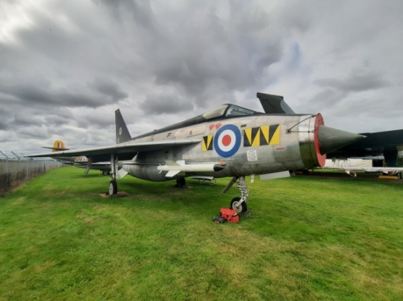 An English Electric Lightining aircraft parked on grass.
